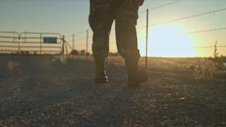 A soldier is walking on a gravel road at sunset thumbnail