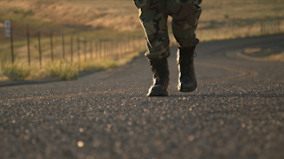 A soldier is walking up a road at sunset thumbnail