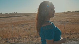 A woman walks down a country road with sunlight shining thumbnail
