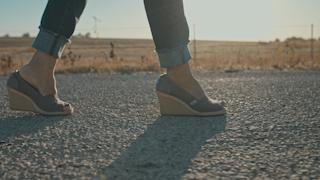 Woman's feet walking down a country road thumbnail