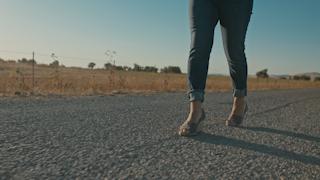 A woman walks down a country road through golden fields thumbnail