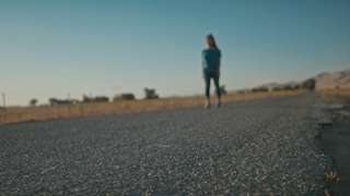 A woman walks down a country road during golden hour thumbnail