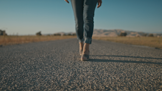 A woman walks down a road out in the country thumbnail