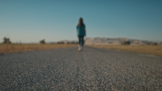 A woman is walking down a country road through golden fields thumbnail