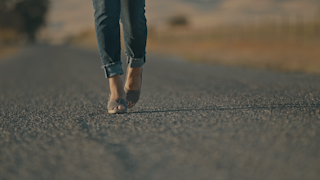 A woman's feet walk down a road out in the country thumbnail