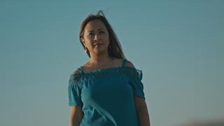 A woman walks down a country road against a blue sky thumbnail