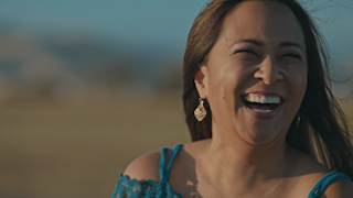 A woman begins to laugh at sunset in the country thumbnail
