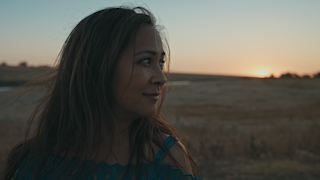 A woman is looking over her shoulder in the country at sunset thumbnail