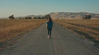 A woman walks down a road during sunset in the country thumbnail