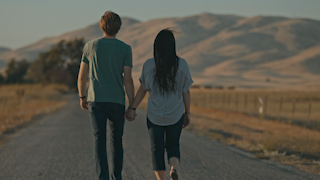 A couple is holding hands and walking down a road at sunset thumbnail