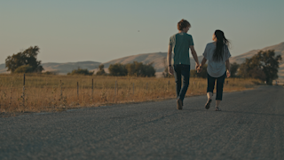 A couple is walking down a road holding hands at sunset thumbnail