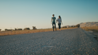 A couple is walking down a road and holding hands at sunset thumbnail