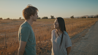A couple is standing on a country road at sunset and smiling at each other thumbnail