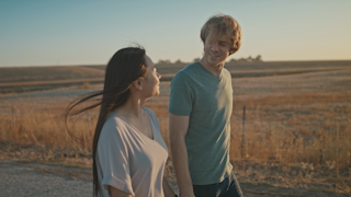 A couple is holding hands and walking down a road at sunset with light flares thumbnail