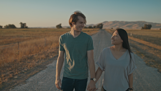 A couple smiles and walks down a country road at sunset thumbnail