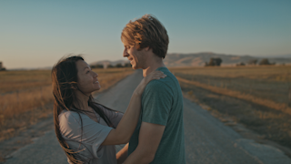 A couple embraces each other on a country road at sunset thumbnail