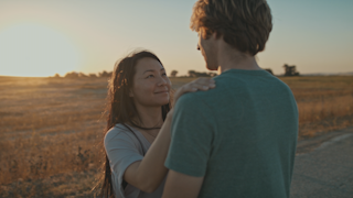 A couple is looking into each others eyes on a road at sunset thumbnail