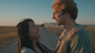 A man and woman run up to eachother on a country road at sunset thumbnail