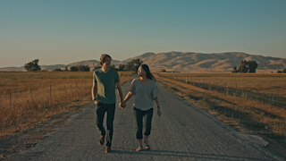 A couple walks joyfully together down a country road at sunset thumbnail