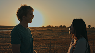 A couple is standing on a country road at sunset and smiling thumbnail