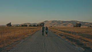 A couple walks down a long country road at sunset underneath a blue sky thumbnail