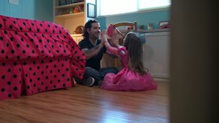 A father and daughter sit on the floor and play thumbnail