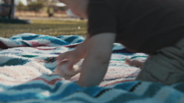 A baby plays with a baseball in a backyard thumbnail