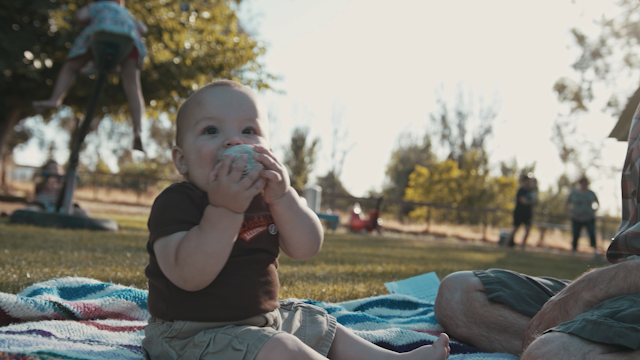 A baby plays with and chews on a baseball in a backyard thumbnail