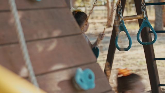 Two little girls are playing on a swing set thumbnail