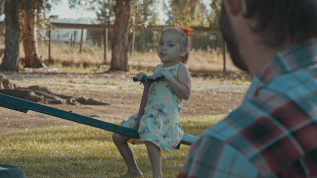 A little girl is sitting on a seesaw thumbnail