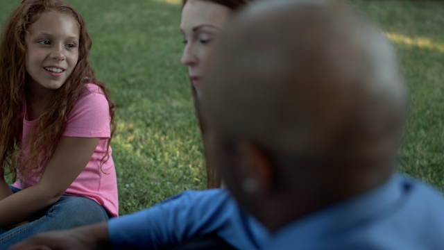 A little girl talks to her parents on the lawn thumbnail