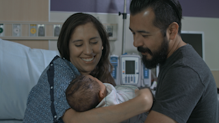 A mother hands her newborn baby to the father thumbnail