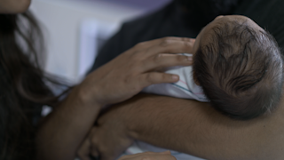 A newborn baby is handed into its fathers arms thumbnail
