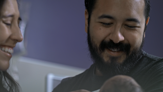 A father looks down at his newborn babay thumbnail