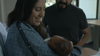 A mother and father hold their newborn baby in a hospital room thumbnail