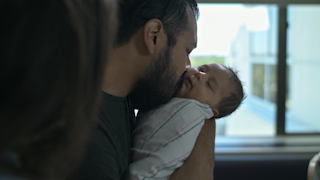 A father holds and kisses his newborn baby thumbnail