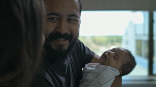 A father holds and kisses his newborn baby in a hospital room thumbnail