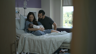 A mother and father admire their newborn baby in a hospital room thumbnail