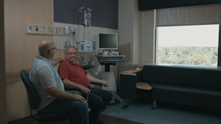 An elderly man is comforted by his son in a hospital room thumbnail