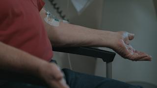 An elderly man has an IV in his arm in a hospital room thumbnail