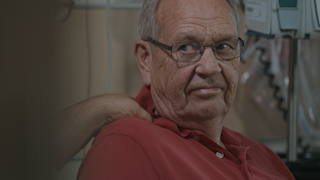 An elderly man sits in a hospital room and is comforted by his son thumbnail