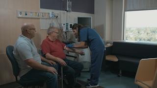 A nurse prepares an IV for an elderly man in a hospital room thumbnail