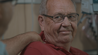 An elderly man is sitting in a hospital room with an IV thumbnail