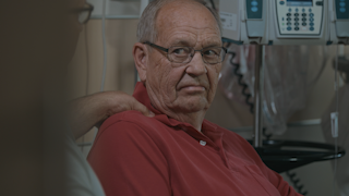 An elderly man seeks comfort from his son in a hospital room thumbnail