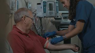 A nurse starts an IV for an elderly man in a hospital room thumbnail