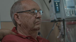An elderly man looks somber while he sits in a hospital room thumbnail