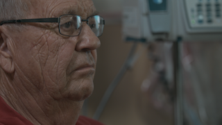 An elderly man has a look of sadness while he sits in a hospital room thumbnail