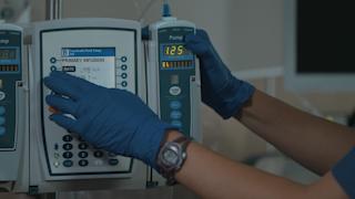 A nurse operates an IV machine in a hospital room thumbnail