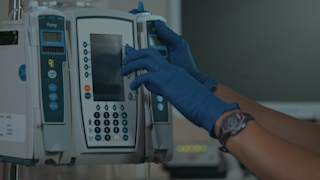 A nurse operates an IV machine thumbnail