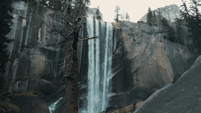 A waterfall flows over a rocky cliff thumbnail